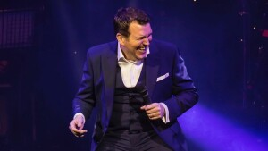 Comedian Tucker performing and laughing at the Cromer Pier Show
